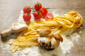 Raw tagliatelle with tomato and porcini mushrooms — Stock Photo