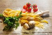 Raw tagliatelle with tomato and boletus — Stock Photo
