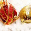 Christmas bauble with ribbon over snow — Stock Photo
