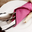 Silverware inside napkin over ceramic plate — Stock Photo