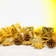 Golden christmas decoration over yellow background — Stock Photo