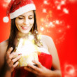 Girl dressed santa claus opens magic box — Stock Photo #36984237