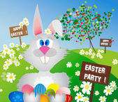 Easter bunny in a meadow with colorful eggs — Stock Photo
