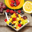 Stock Photo: Greedy fruit salad with red fruits on wood
