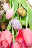 Easter concept with pink tulips, bird nest and decorative eggs — Zdjęcie stockowe