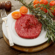 Stock Photo: Raw hamburger  with tomato, herbs and pink pepper