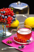 Red fruits tea over black background — Stock Photo