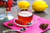 Red fruits tea with berries on cake stand — Stock Photo
