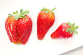 Three  strawberries over white ceramic plate — Stock Photo