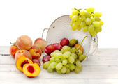 Fresh summer fruits inside ceramic colander — Stock Photo