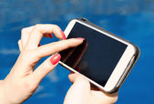 Female finger touching smartphone screen — Stock Photo