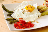 Fried egg with steamed asparagus — Stock Photo