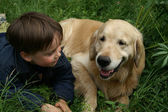 The boy and his dog lay on the grass — Stock Photo