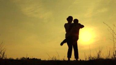 Mum swings son at sunset — Stock Video