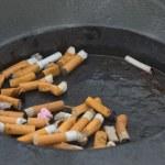 Public ashtray with smoked cigarettes — Stock Photo