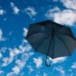 Stock Photo: Black umbrellagainst cloudy sky
