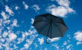 Black umbrella against a cloudy sky — Stock Photo