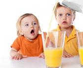 Happy children drink orange juice isolated on white — Stock Photo