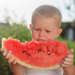 Little baby eating watermelon outdoors — Stock Photo #23906615