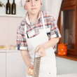 Happy little boy making pizza dough — Stock Photo