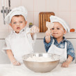 Happy little chefs preparing dough in the kitchen — Stock Photo #25530393