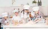 Happy little chefs preparing dough in the kitchen — Stock Photo