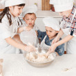 Happy little chefs preparing dough in the kitchen — Stock Photo #26041433