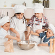 Happy little chefs preparing dough in the kitchen — ストック写真