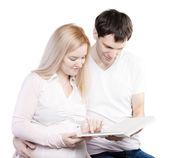 Young happy couple with photo album — Stock Photo