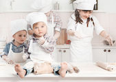 Happy little chefs preparing dough in the kitchen — Stock Photo