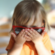 Little girl in red glasses — Stock Photo