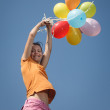 Beautiful and athletic Girl jumping with balloons on a green meadow — Stock Photo #28746355