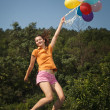 Beautiful and athletic Girl jumping with balloons on a green meadow — Stock Photo #28781221