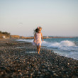 Silhouette of adorable little girl on a beach at sunset — Stock Photo