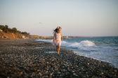 Silhouette di adorabile bambina su una spiaggia al tramonto — Foto Stock