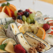 Delicacies. Food composition - hard and soft cheese varieties and fruits. — Stock Photo