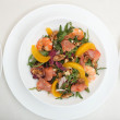 Fresh mixed salad with nuts, shrimps, salmon and peaches close up — Stock Photo
