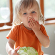 Little girl eats cabbage — Stock Photo