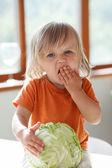 Klein meisje eet kool — Stockfoto