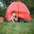Boy looks out from a tent — Stock Photo