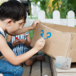 Foto Stock: Little boy painting paints