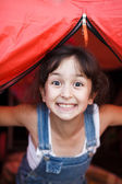 Girl looks out from a tent — Stock Photo