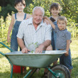 Children is helping her Grandfather in the garden — Stock Photo #32110869