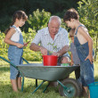 Children is helping her Grandfather in the garden — Stock Photo #32313095