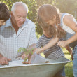 Children is helping her Grandfather in the garden — Stock Photo #32313349