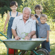 Children is helping her Grandfather in the garden — Stock Photo #32313383
