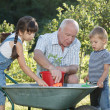 Stock Photo: Children is helping her Grandfather in garden
