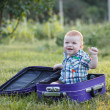 Small boy sitting on an old suitcase — Stock Photo