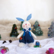 Christmas toy rabbit on background trees — Stock Photo #33497041
