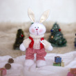 Christmas toy rabbit on background trees — Stock Photo #33497075